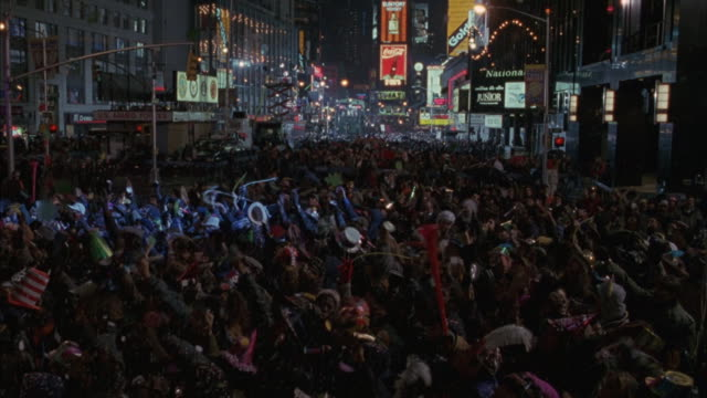 high angle down with slight pan up. new year's eve in times square. large celebration with crowd cheering, waving party hats, horns. - street party stock videos & royalty-free footage