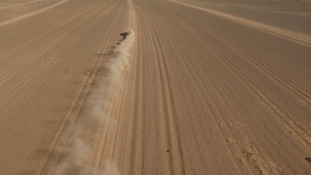 High angle drone footage of off-road vehicle moving through arid landscape