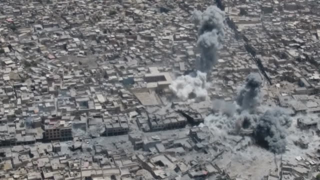 high angle drone footage showing airstrikes in mosul, iraq with explosions, smoke plumes and fire balls. - air raid stock videos & royalty-free footage