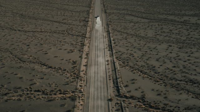 high angle drone shot following behind a truck driving on a dusty dirt road, nevada, united states of america - ländliche straße stock-videos und b-roll-filmmaterial