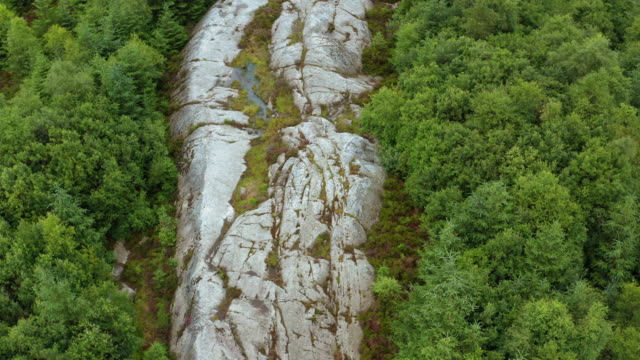 high angle drone view of a granite outcrop in a remote part of rural south west scotland - johnfscott stock videos & royalty-free footage