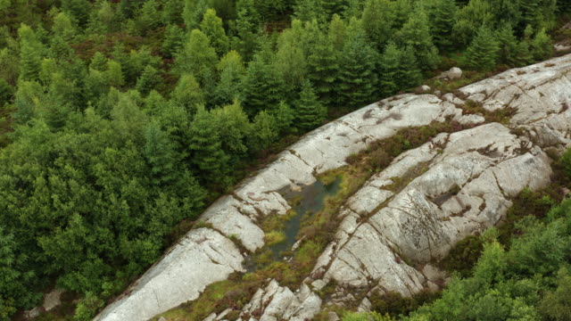 high angle drone view of a large granite outcrop in a remote part of rural south west scotland - remote location stock videos & royalty-free footage