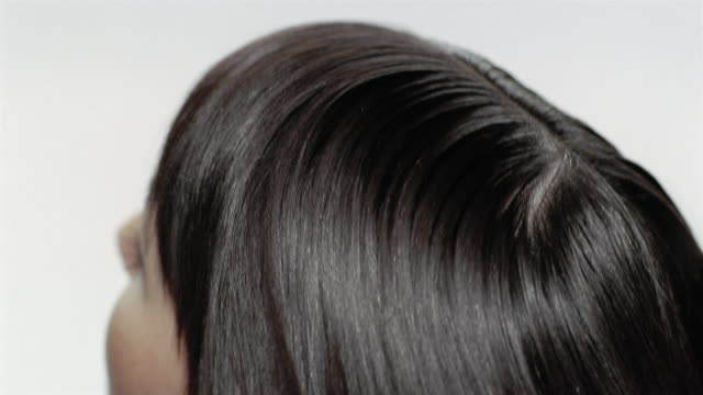 High angle extreme close up back of head of woman with long, dark hair / shaking head back and forth