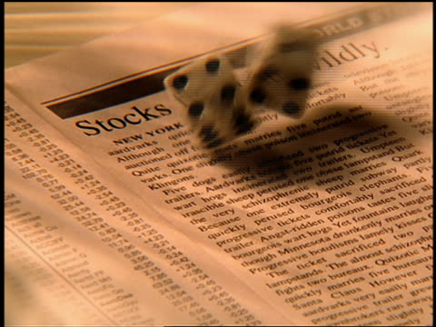vídeos y material grabado en eventos de stock de high angle extreme close up dice rolling onto page with stock prices + newspaper article - enfoque de objetos sobre la mesa