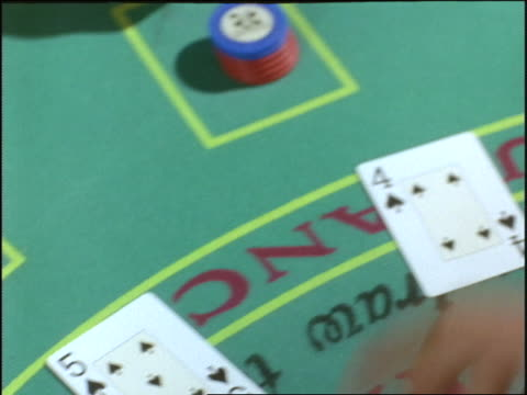 high angle extreme close up pan hands of card dealer dealing cards to players at blackjack table - blackjack stock videos and b-roll footage