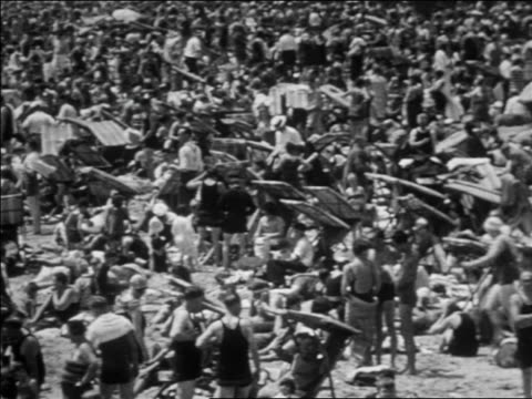 b/w 1930 high angle pan extremely crowded beach at coney island / nyc / documentary - coney island brooklyn stock videos & royalty-free footage