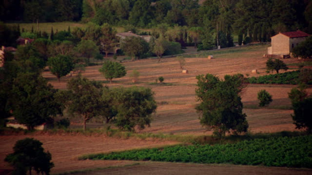 vidéos et rushes de high angle pan farm buildings + several fields with crops growing / seillans, provence  france - patchwork landscape