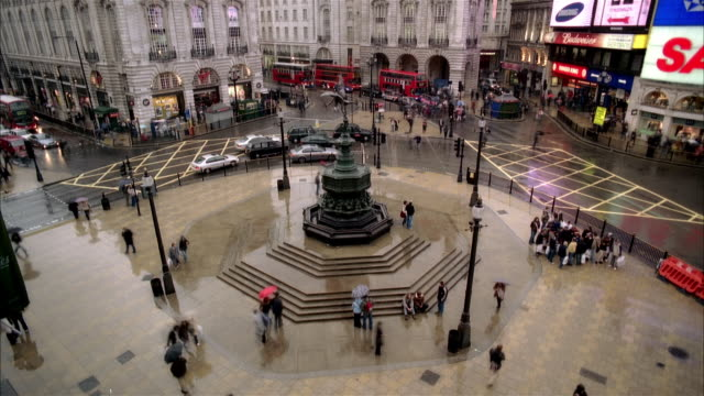 high angle fast motion wide shot traffic moving around eros statue in piccadilly circus/ london - large scale screen stock videos & royalty-free footage