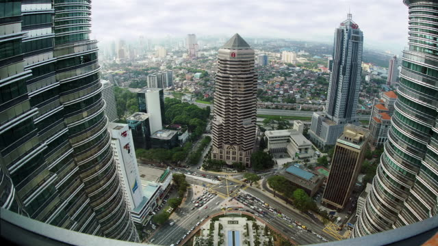 high angle fast motion wide shot view of menara public bank and traffic from petronas twin towers/ kuala lumpur - kuala lumpur stock videos & royalty-free footage
