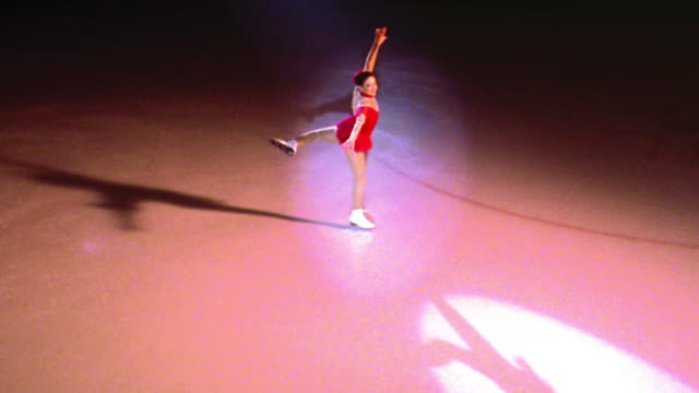 high angle female figure skater in red costume skating, turning + posing gracefully in spotlight
