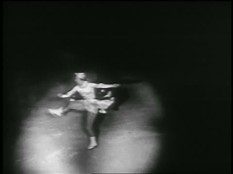 b/w 1935 high angle female figure skater in spotlight spinning with one leg up / canada - 1935 stock videos and b-roll footage