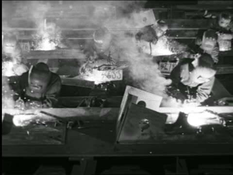 b/w 1943 high angle female welders working in rows in factory + removing masks / industrial - steel worker stock videos & royalty-free footage