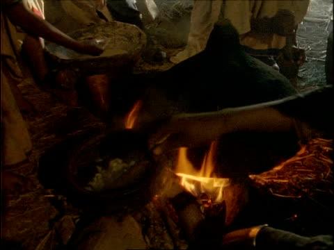 vídeos y material grabado en eventos de stock de cu high angle, food being cooked over traditional african fire, ethiopia, africa - hambriento