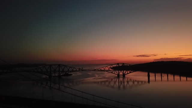 high angle forth bridge at sunrise - fluss firth of forth stock-videos und b-roll-filmmaterial