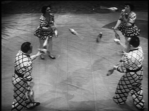 b/w 1955 high angle four people in costumes juggling pins back + forth in circus - jonglieren stock-videos und b-roll-filmmaterial