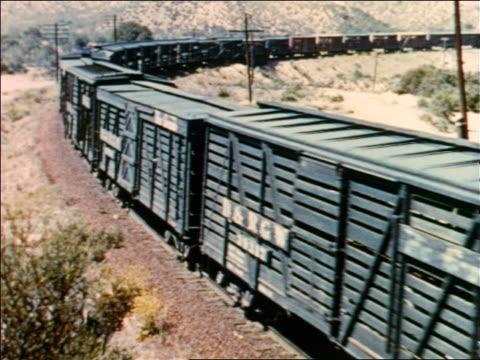 1954 high angle freight train rounding curve in desert-like area / industrial - 1954 stock-videos und b-roll-filmmaterial