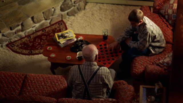 vídeos y material grabado en eventos de stock de high angle pan from fireplace to senior man + boy playing checkers on coffee table - mesa baja de salón