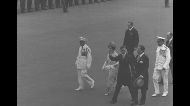 high angle george vi queen elizabeth walk and wave accompanied by naval officers / large crowd cheering and tossing hats in front of the british... - 1939 stock-videos und b-roll-filmmaterial