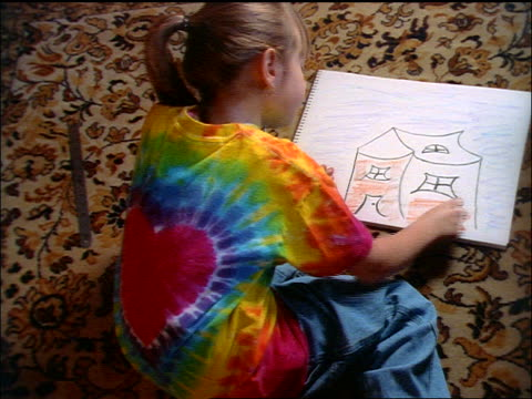 high angle girl wearing tie-dye t-shirt sitting on rug doing drawing of house