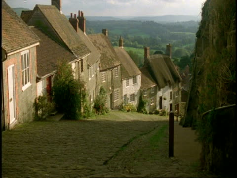 ms high angle, gold hill, shaftesbury, dorset - cobbled street with row of cottages/homes - strohdach stock-videos und b-roll-filmmaterial