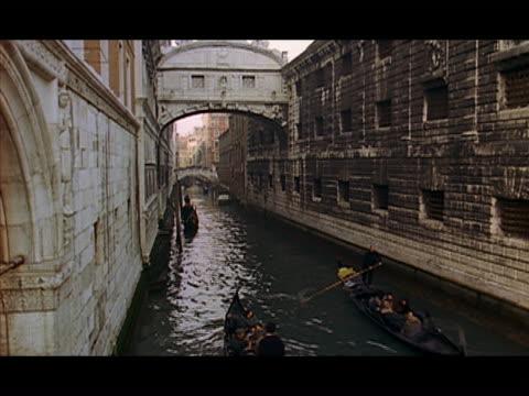 vídeos de stock e filmes b-roll de high angle gondoliers rowing gondolas along canal / venice, italy - formato letterbox