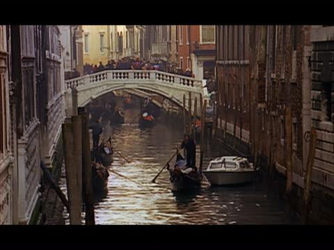 vidéos et rushes de high angle gondoliers rowing gondolas along canal / venice, italy - format vignette