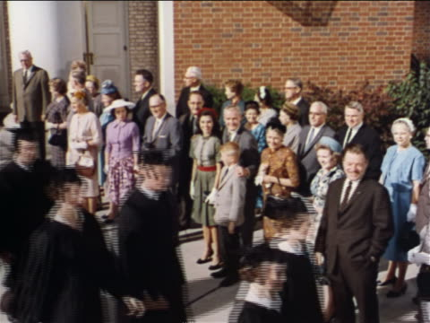 1962 high angle graduates walking past crowd of onlookers outdoors / industrial - schul oder uniabschluss stock-videos und b-roll-filmmaterial