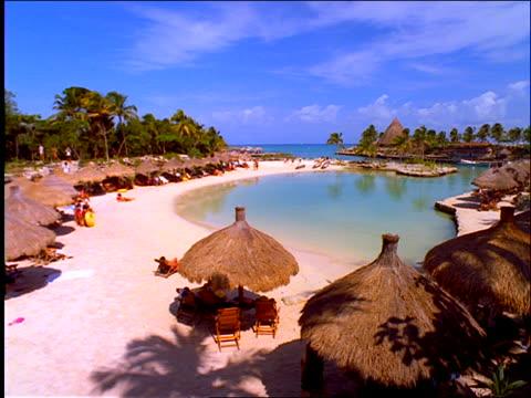 vidéos et rushes de high angle pan of grass umbrellas on beach on lagoon / cancun - angle de prise de vue