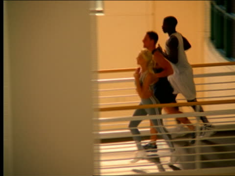 stockvideo's en b-roll-footage met high angle pan group jogging on elevated track in health club - gymbroek