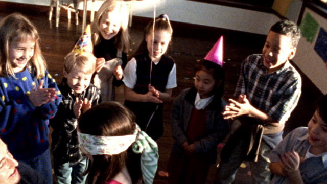 high angle group of children with birthday hats clapping around blindfolded girl being spinned for pinata - papier stock videos & royalty-free footage