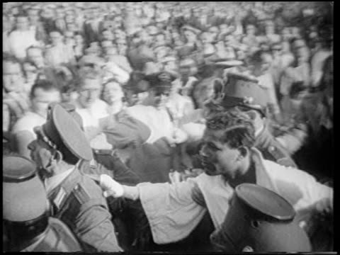 b/w 1951 high angle pan group of german policemen leading sugar ray robinson thru crowd after boxing match - 1951 stock videos & royalty-free footage