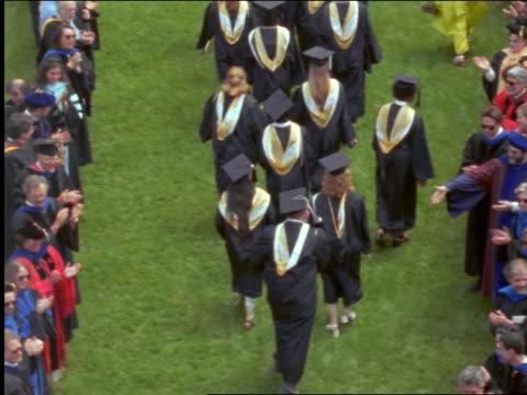 vídeos de stock, filmes e b-roll de rear view high angle group of graduates recessing past crowd who congratulates them - 1990 1999
