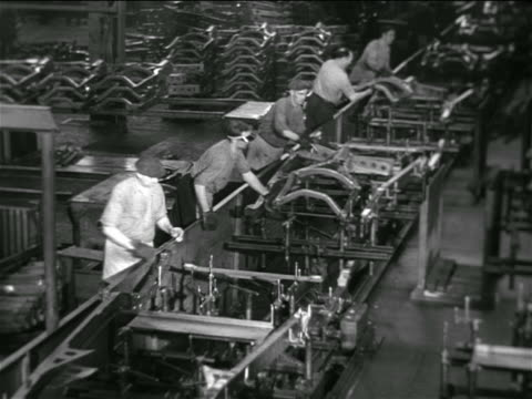 stockvideo's en b-roll-footage met b/w 1936 high angle group of men working with machinery on conveyor belt in chevrolet car factory - assemblagelijn