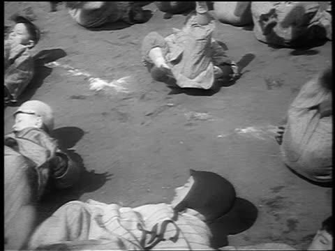 b/w 1941 high angle group of small boys in baseball uniforms exercising on backs lying on ground / nyc - baseball diamond stock videos & royalty-free footage