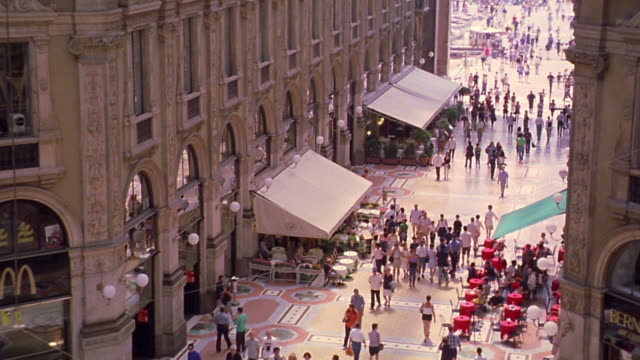 high angle groups of people walking from Piazza Duomo in Galleria Vittorio Emanuele / Milan, Italy
