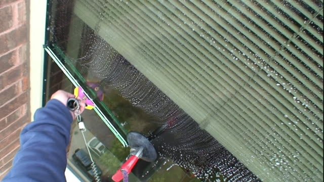 high angle hand-held - a window washer uses a squeegee to clean a window of a high-rise office-building. / wisconsin, usa - window washer stock videos & royalty-free footage