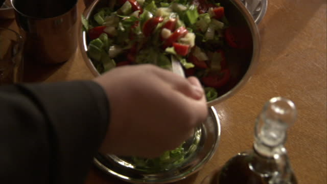 High Angle hand-held - Hands dish salad onto a plate near a carafe of oil. / Greece