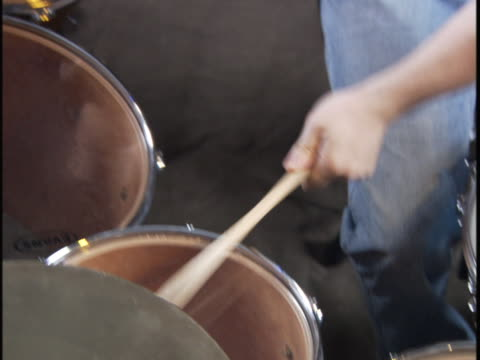 vidéos et rushes de high angle handheld medium shot of a young man as he plays the drums - rock moderne