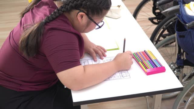 vídeos de stock, filmes e b-roll de visão de mão de alto ângulo: uma adolescente com síndrome de down fazendo lição de casa ou tarefa na sala de aula com amigos deficientes na escola de rodas. as meninas estão sentadas em uma mesa, escrevendo, desenhando arte em papel com lápis de co - só uma adolescente menina