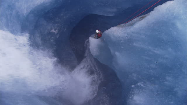 """""""High Angle hand-held-A waterfall crashes past an ice climber who rappels into a crevasse. / Alaska, USA"""""""