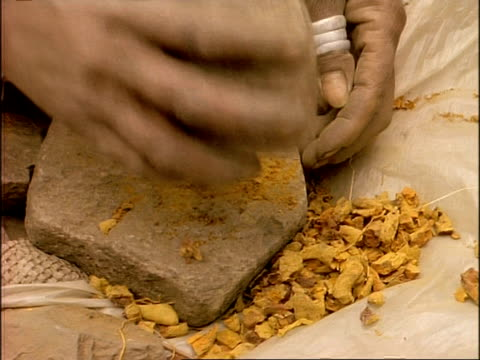 cu high angle, hands using rocks to crush dry, orange substance, ethiopia, africa - mortar and pestle stock videos and b-roll footage