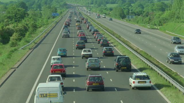 rear view high angle heavy highway traffic driving away from camera / near london, england - film moving image stock videos & royalty-free footage