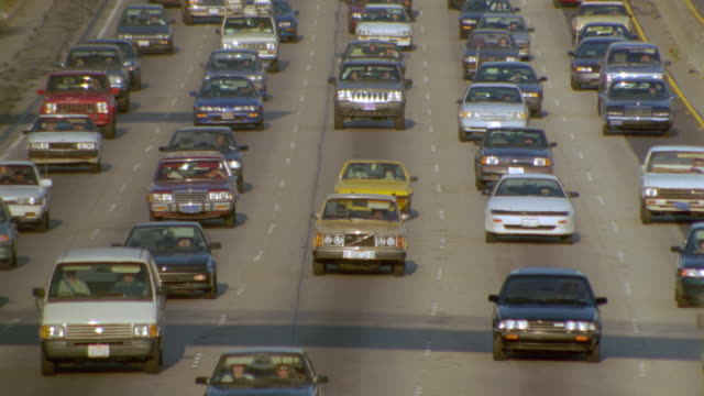 vídeos y material grabado en eventos de stock de high angle heavy traffic driving towards camera on santa monica freeway / los angeles - 1996