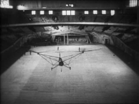 stockvideo's en b-roll-footage met b/w 1937 high angle helicopter (focke achgelis fa 61) hovering in berlin stadium, germany / industrial - 1937
