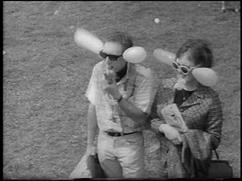 b/w 1967 high angle hippie couple with balloons attached to sunglasses standing at bein / detroit - bizarre fashion stock videos and b-roll footage