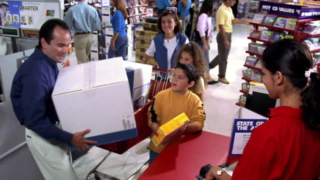 CANTED high angle Hispanic family buying computer + software at checkout with female cashier