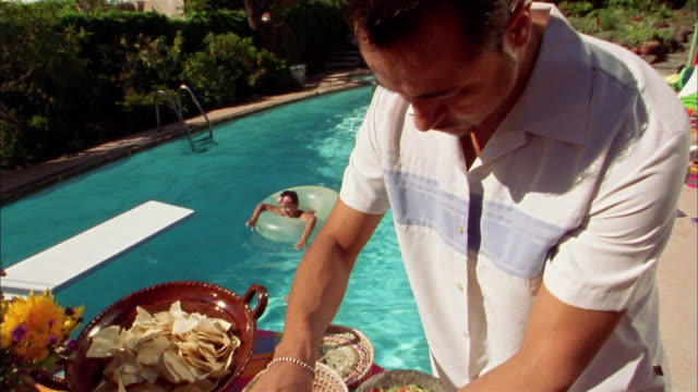 high angle hispanic man making a taco from buffet by swimming pool / boy in inner tube in background - taco stock videos & royalty-free footage