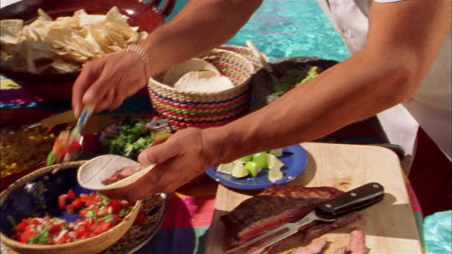 stockvideo's en b-roll-footage met high angle hispanic man making a taco from buffet by swimming pool / boy stealing taco from hand - mischief