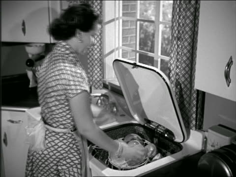 b/w 1950 high angle housewife taking dishes out of dishwasher - lavastoviglie video stock e b–roll