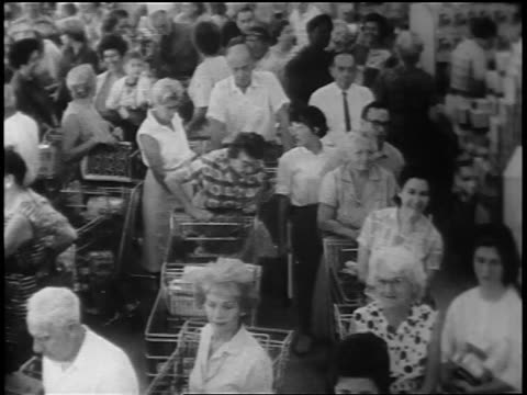 stockvideo's en b-roll-footage met b/w 1962 high angle huge crowd with shopping carts waiting in line at grocery store / cuban missile crisis - 1962